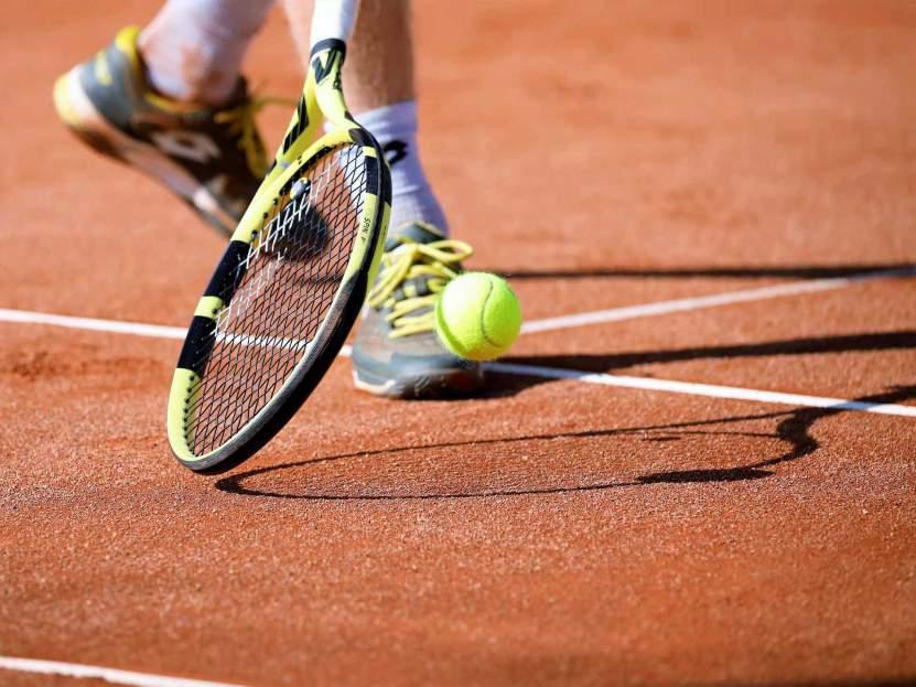 Ein Tennisschläger schlägt auf Ball am Platz